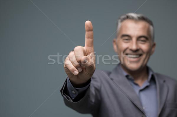 Smiling businessman using a virtual interface Stock photo © stokkete