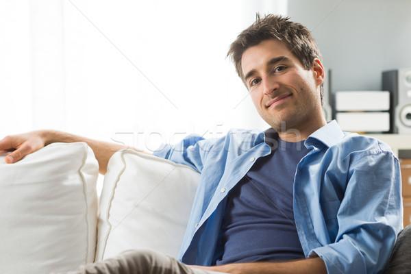 Jonge man ontspannen sofa glimlachend woonkamer home Stockfoto © stokkete