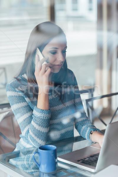 Fiatal nő telefonbeszélgetés dolgozik számítógép ablak telefon Stock fotó © stokkete