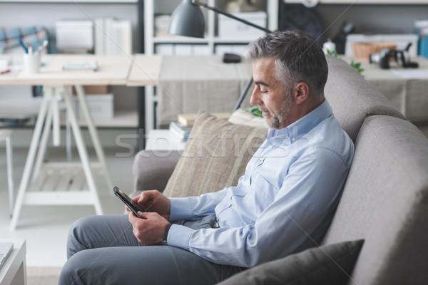 Imprenditore smartphone seduta divano touch screen Foto d'archivio © stokkete
