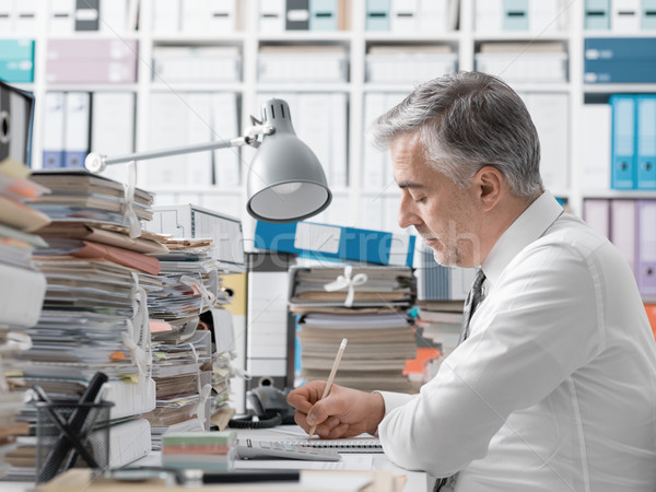 Businessman working in the office and piles of paperwork Stock photo © stokkete