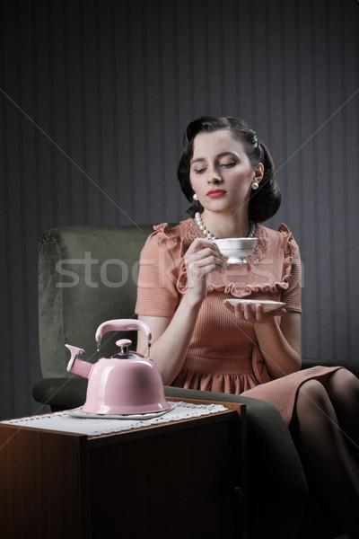 Gyönyörű nő iszik tea ül fotel nő Stock fotó © stokkete