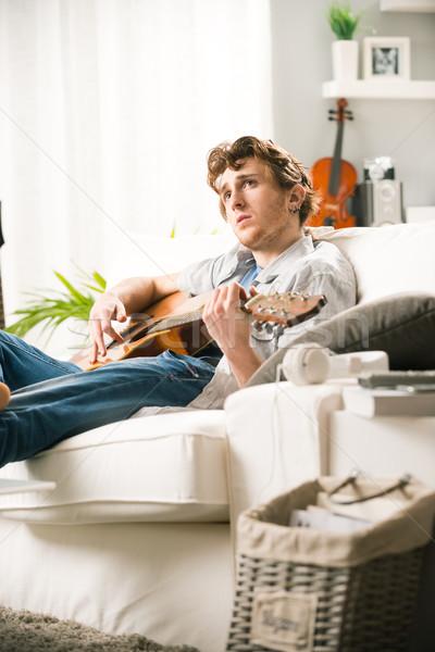 Dal fiatalember játszik gitár ül kanapé Stock fotó © stokkete