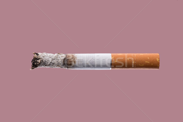 Cigarette burning on pink background Stock photo © stokkete