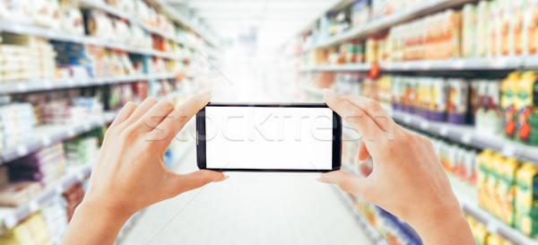 Woman using a smartphone at the supermarket Stock photo © stokkete