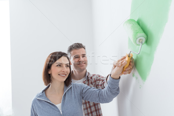 Loving couple painting a room Stock photo © stokkete