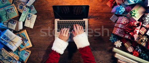 Santa typing on a laptop Stock photo © stokkete