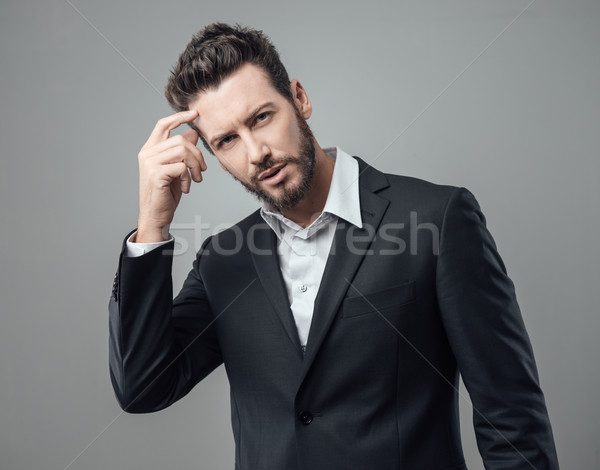 Confused businessman touching temples Stock photo © stokkete