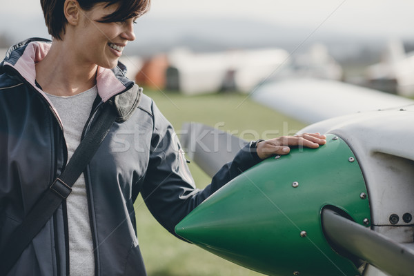 Female pilot posing with her plane Stock photo © stokkete