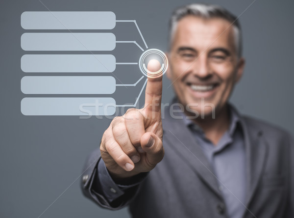 Businessman using a virtual touch screen interface Stock photo © stokkete