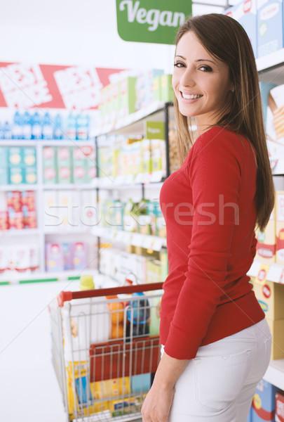 Foto stock: Sorrindo · compras · empurrando · completo · carrinho