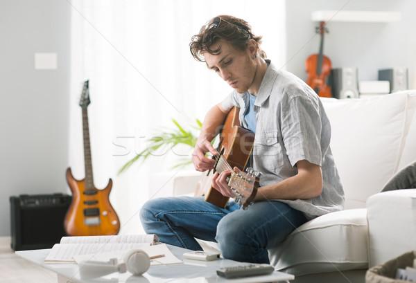 песня молодым человеком играет гитаре сидят диван Сток-фото © stokkete