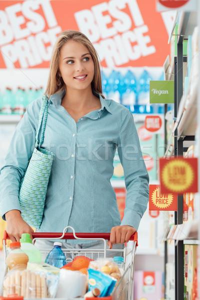 Stockfoto: Vrouw · voortvarend · winkelwagen · jonge · glimlachende · vrouw · supermarkt