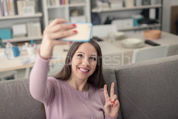 Cute girl using a smartphone Stock photo © stokkete