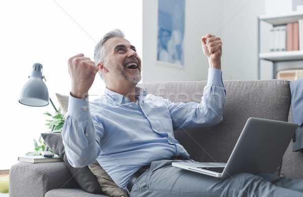 Cheerful businessman with raised fists Stock photo © stokkete