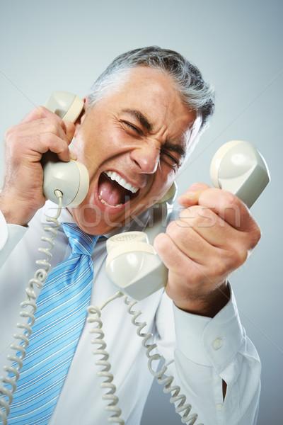 Businessman yelling into phone Stock photo © stokkete