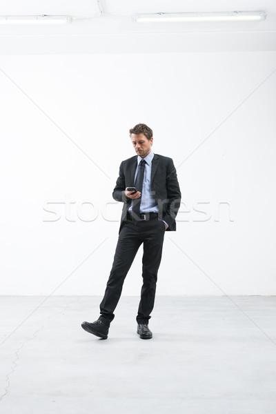 Zakenman wachten mobiele telefoon elegante lege kamer Stockfoto © stokkete