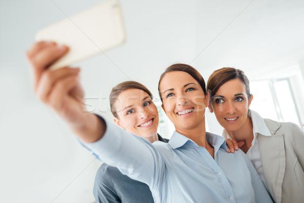 Smiling business women team taking a selfie Stock photo © stokkete
