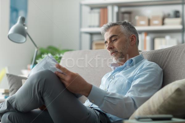 üzletember olvas újság otthon ül kanapé Stock fotó © stokkete