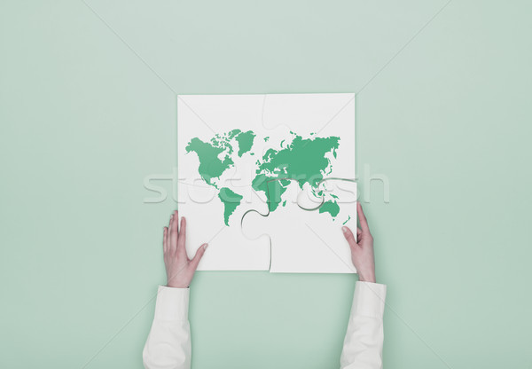 Woman completing a puzzle with a world map Stock photo © stokkete
