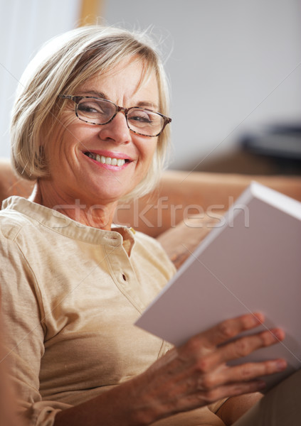 Relajante casa sonriendo altos mujer lectura Foto stock © stokkete