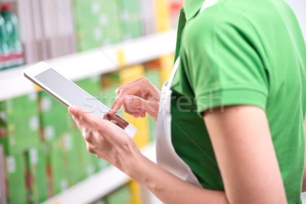 Sales clerk using tablet Stock photo © stokkete