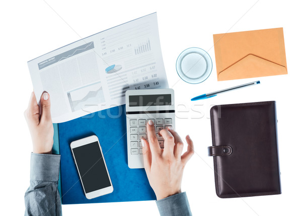 Business woman using a calculator Stock photo © stokkete