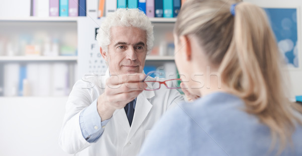 Ophthalmologist giving glasses to the patient Stock photo © stokkete
