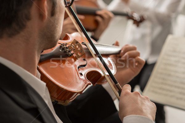 Violinist performing on stage with orchestra Stock photo © stokkete