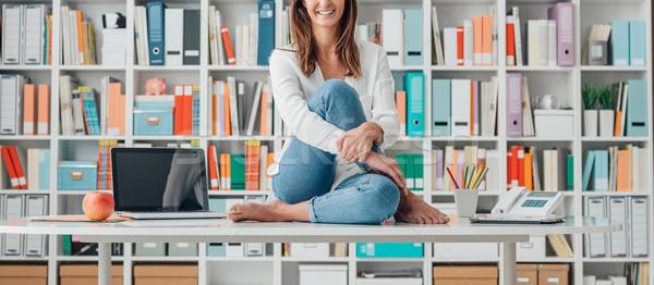 Gülümseyen kadın oturma üst büro genç kadın ofis Stok fotoğraf © stokkete
