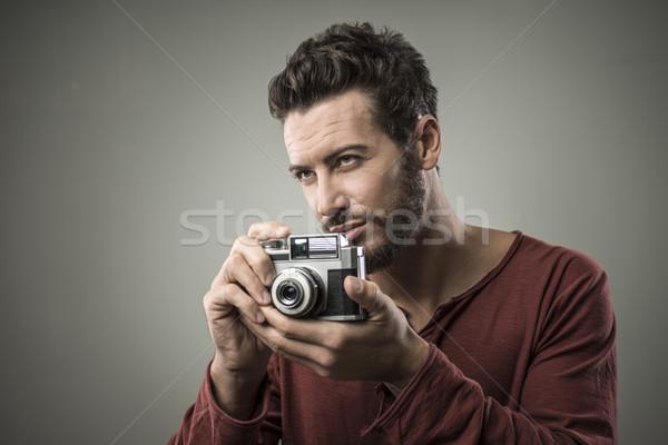 Férfi tart régi fényképezőgép mosolyog fiatalember öreg Stock fotó © stokkete
