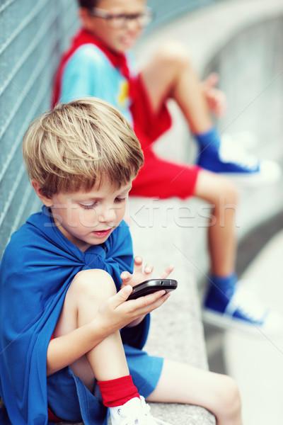 Little Superhero with smartphone Stock photo © stokkete