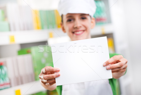 Sales clerk holding a white card Stock photo © stokkete