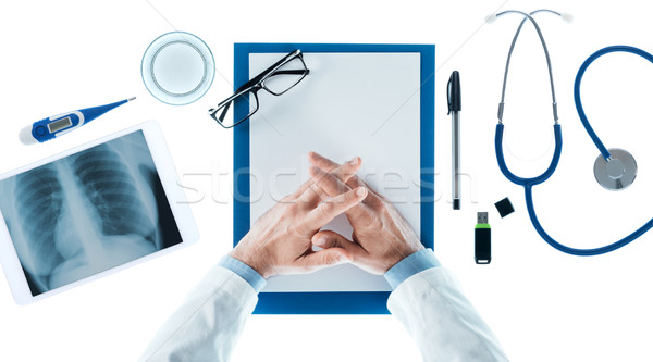 Doctor with hands clasped waiting at desk Stock photo © stokkete