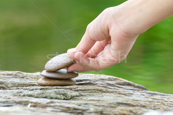 Hand put stone building a pile of zen stones Stock photo © stoonn