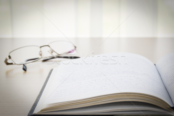 Book and eyeglasses with on the desk Stock photo © stoonn