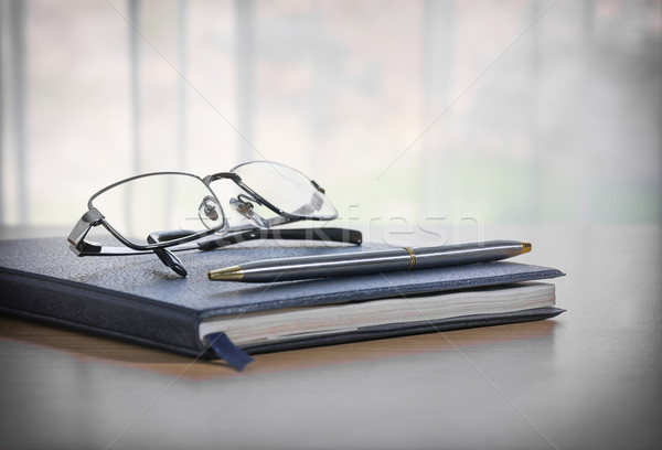 Glasses and pen on a book Stock photo © stoonn