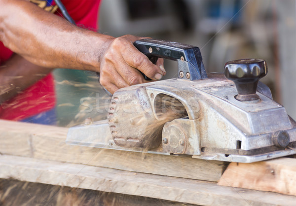 Carpenter working with electric planer Stock photo © stoonn