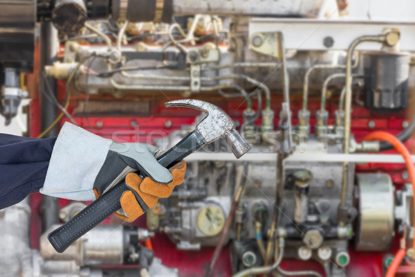 Hand in glove holding hammer with engine Stock photo © stoonn