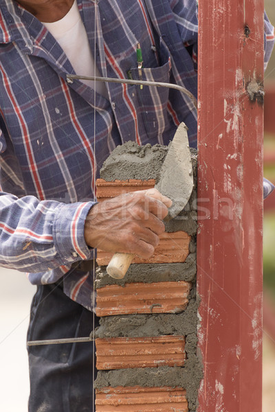 Stock photo: Bricklayer working in construction site of  brick wall
