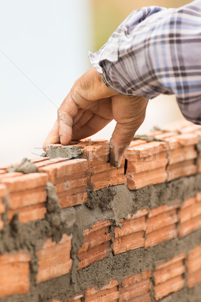 Bricklayer working in construction site of a brick wall Stock photo © stoonn