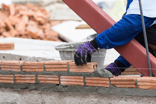 Stock photo: Bricklayer working in construction site of a brick wall