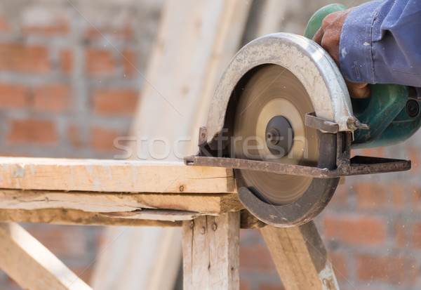 Stock photo: Carpenter using circular saw in loggers