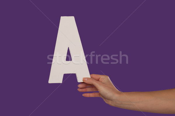 Female hand holding up the letter A from the right Stock photo © stryjek