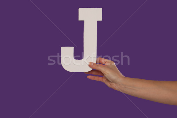 Female hand holding up the letter J from the right Stock photo © stryjek