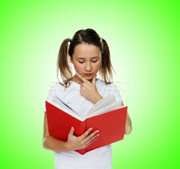 Smart cute girl reading from a red book Stock photo © stryjek