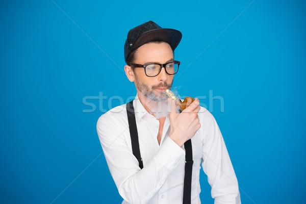 man wearing shirt and hat smoking e-pipe Stock photo © stryjek
