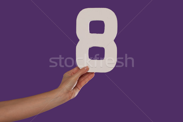 Female hand holding up the number 8 from the left Stock photo © stryjek