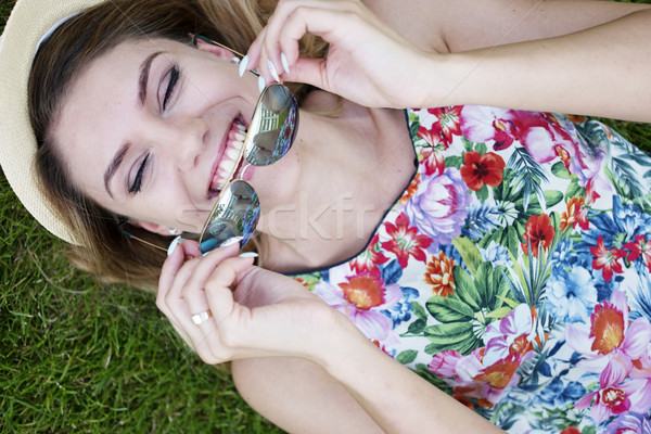 Happy Woman Holding Shades While Lying on Grasses Stock photo © stryjek