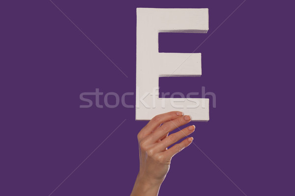 Female hand holding up the letter E from the bottom Stock photo © stryjek